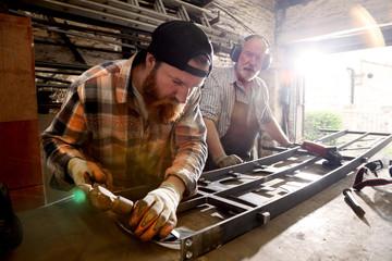 Senior blacksmith and son hammering metal on workbench in blacksmiths shop