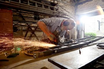 Blacksmith grinding metal on workbench in blacksmiths shop
