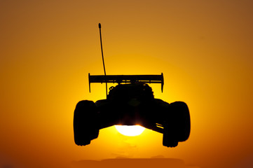 This image is shows a remote controled car on a sunset