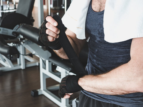 Stylish, muscular man with a white towel on his shoulders and black sports gloves, preparing for strength training. Concept of healthy lifestyle, strength and motivation