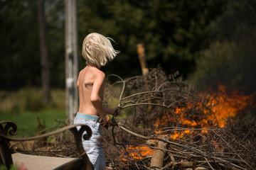 Blond haired boy placing tree branch onto garden bonfire