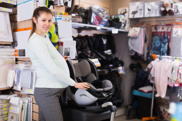 Pregnant woman customer is looking baby chair for car