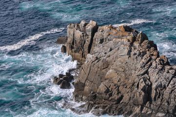 Vue sur les vagues qui s'écrasent sur les rochers comme découpés en Bretagne