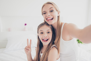 Indoors domestic lifestyle grimace fooling concept. Close up portrait of cute cool funky funny beautiful pretty excited rejoicing delightful mom and offspring making taking self picture in bed room
