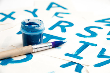 Alphabet drawing. Process of creating watercolor font. Blue gouache in the jar and brush on background with blue colored letters.
