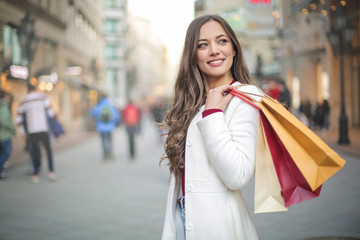 Beautiful woman walking in the street, holding shopping bags