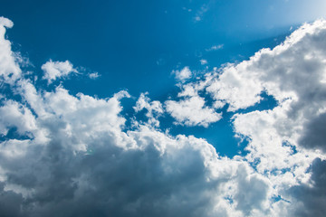 Scenic view at blue sky with clouds. Abstract nature background. Dramatic sky with fluffy clouds. Sunny day.