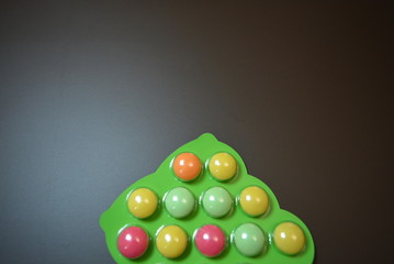 Bright green plate of baby vitamin tablets on a matte brown background