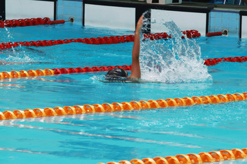 Young swimmer practice backstroke or back crawl in swimming pool for competition or race