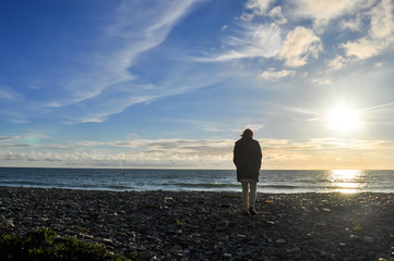 Silhouette de femme sur la plage devant l'horizon, le soir face au soleil