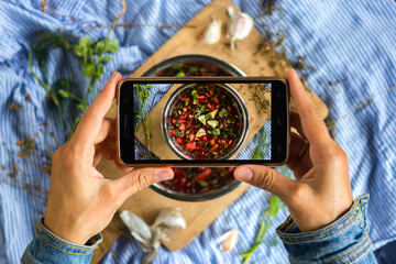 Woman hands take smartphone food photo of cherry cold chrianteli soup. Phone food photography for social media or blogging in popular and trendy top view style. Raw vegan vegetarian meal concept.