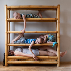 Young mother with three children in empty apartment was placed on shelves of bookcase. Kid and mom are happy together. Concept of compact housing.