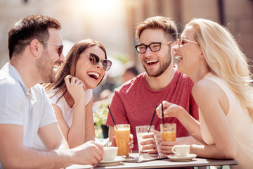Four laughing friends enjoying coffee in a cafe