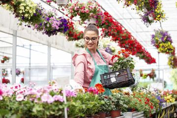 Young woman holding crate on hand with flowers