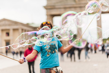 Street performer, busker, entertaining the crowd in front of the Brandenburg Gate in Berlin on an overcast summer day. Colorful soap bubbles floating in the foreground.