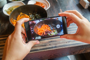 Taking Food Photo of Traditional Korean Dish Bibimbap Served Along With Small Side Dishes Clled Banchan on Mobile Phone. Asian Authentic Cuisine