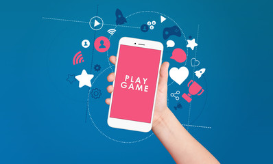 Kid hand holding smartphone with play game text on screen with award and achievement icons on blue background. Gamification concept
