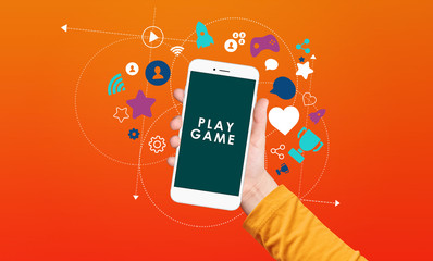 Kid hand holding smartphone with play game text on screen with award and achievement icons on orange background. Gamification concept