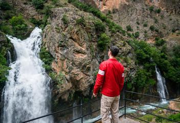 Traveler looking at powerful waterfalls in mountains