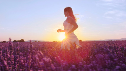 SLOW MOTION: Young woman running through lavender field at sunset