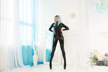 luxury caucasian beautiful fashion girl, dressed in a black fetish catsuit, standing on a background of white window alone
