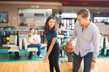 Smiling Boy Teaching Friend To Play Bowling In Club