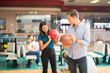 Boy Showing Friend How To Play Bowling In Club