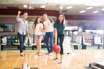 Friends Motivating Teen Girl Throwing Bowling Ball At Alley