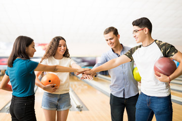 Smiling Teenage Friends Stacking Hands At Bowling Club