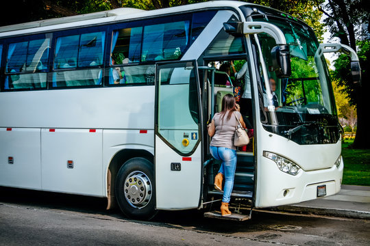 transport, tourism, road trip and people concept - passenger boarding to travel in bus