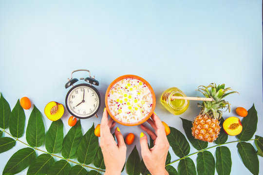 morning breakfast, girl's hands holding muesli, fruit, honey, pineapple, peaches, alarm clock on blue background with green leaves Copyspace