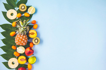 morning breakfast, fruit, peaches, pineapple, kiwi, lime on a blue background with green leaves Healthy breakfast freshness Flat lay Top view Copyspace