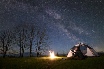 Beautiful night camping in mountains. Young male backpacker with photo camera sitting alone in front of tourist tent at burning campfire on grassy valley under night blue starry sky with Milky way