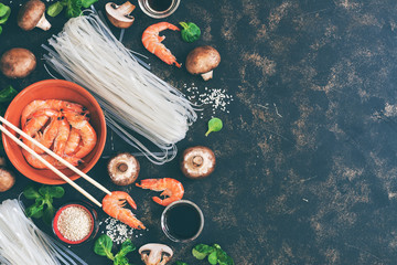 Background with Asian ingredients - rice noodles, shrimps, mushrooms, sesame, salad corn, dark background. Flat lay,copy space. toned photo
