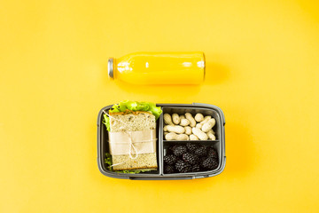 Lunchbox with food - sandwich, nuts and berries - next to a bottle of orange juice on a yellow background. Top view, flat lay,