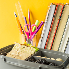 Lunchbox with food - a sandwich, nuts and berries stands next to a stack of books and a glass with pens and pencils. Meals during study
