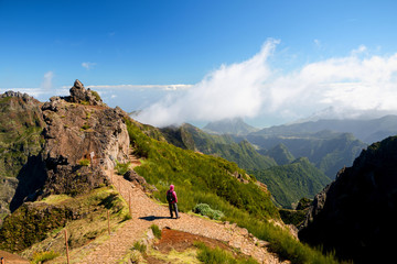 Woman alone looking at valley and mountains in sunny weather, Ninho da Manta, Pico do Areeiro, Madeira island, Portugal Fototapete