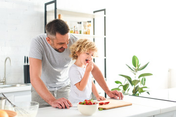 smiling father standing near son while he eating strawberry at kitchen