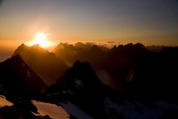 True Lofoten midnight sun over sharp mountains of Moskenesoya and fjords, seen from Munken peak summit, Norway