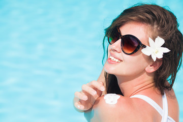 Young longhaired woman in sunglasses and with flower putting sun cream on shoulder