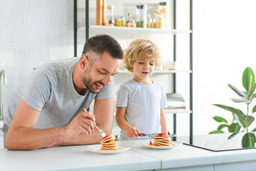 happy father and son eating pancakes at kitchen