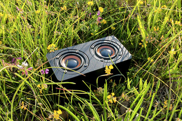 close-up of a portable audio speaker in the grass, freedom of movement listening to music outdoors to relax and have fun