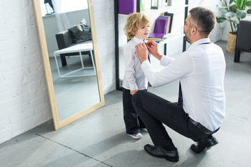 rear view of father helping son tying necktie at home