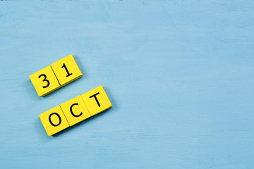 OCT 31, yellow cube calendar on blue wooden surface with copy space