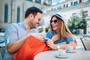 Beautiful loving couple sitting in a cafe enjoying in coffee and conversation after shopping