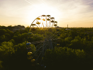 aerial amazing magic view of ferris wheel during sunset golden hour in the park with lots of trees
