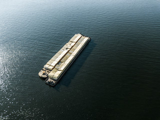 aerial drone shot cargo ship parked in the bay on a sea water texture