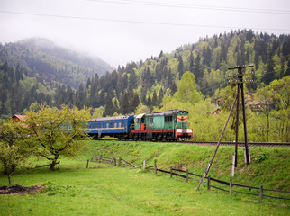 In the mountains a green locomotive with blue wagons. The train goes to the Carpathians