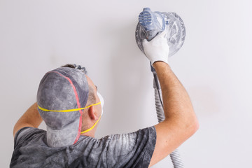 Plasterer wearing dust mask polishes a wall with sanding machine . House renovation concept.