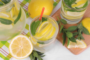 Homemade lemonade with lemon and mint in a glass jug and a glass next to fresh lemon on a white wooden background